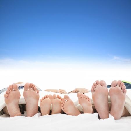 familie slapen op het bed met blauwe hemel achtergrond