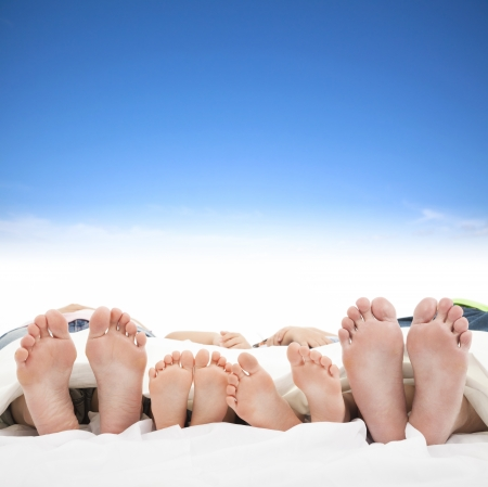 bed feet: family sleeping on the bed with blue sky background