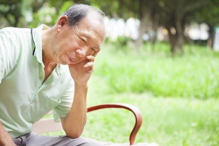 depresso anziano uomo seduto nel parco photo