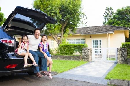 familie: glückliche Familie sitzt im Auto und ihr Haus hinter