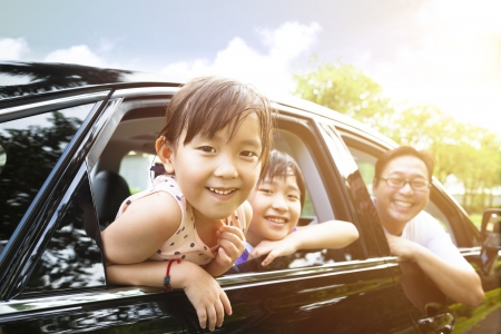 holiday: happy little girl with family sitting in the car