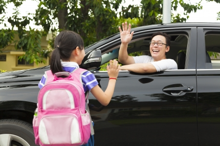 goodbye: little girl say good bye with father in front of school