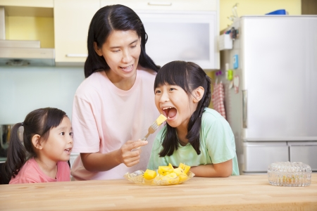 Mother and daughter eating fruits in the kitchen photo