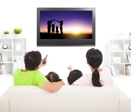 Familie kijken naar de tv in de huiskamer Stockfoto - 21857073