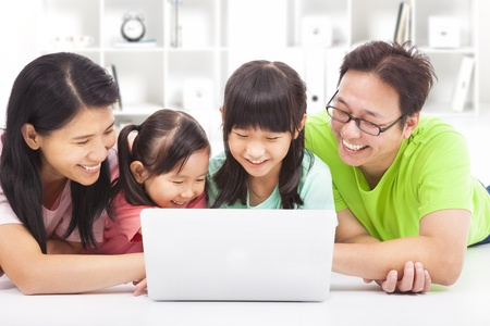 happy family with children looking at laptop photo