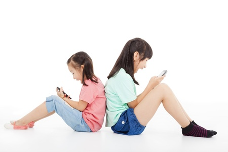 kid sitting: two happy little girls playing smart phone Stock Photo