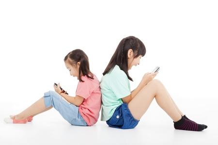 spielen: zwei glückliche kleine Mädchen spielen Smartphone
