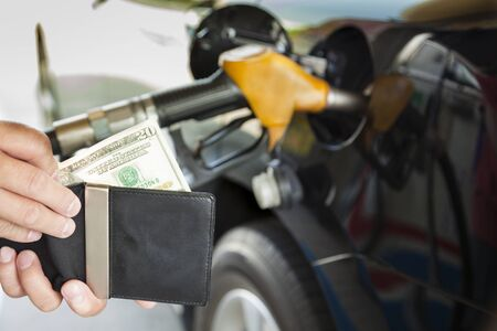 refueling: man counting money with gasoline refueling car at fuel station Stock Photo