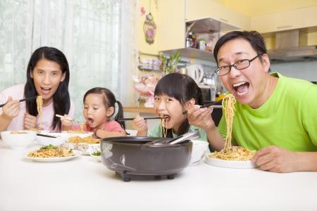 ätande: Lycklig asiatisk familj äta nudlar Stockfoto
