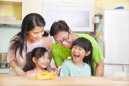 children breakfast: happy family and daughter eating fruits in the kitchen