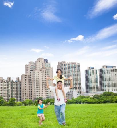 asia family: familia feliz corriendo en el parque de la ciudad Foto de archivo