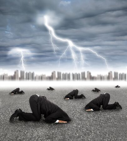 storm coming: scared businessman hiding on the ground with storm coming