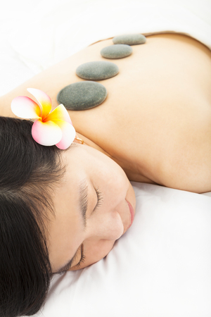 relaxed woman in spa salon with  stones photo