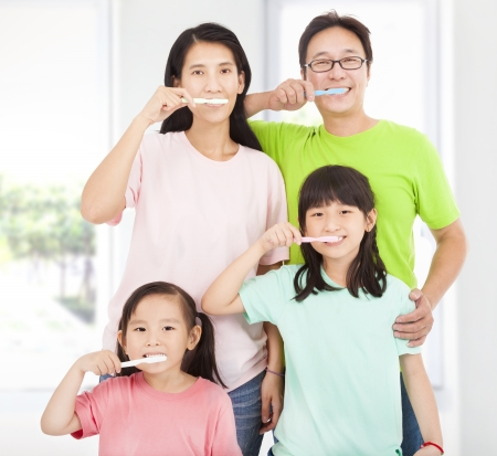 bathroom woman: happy family brushing her teeth Stock Photo