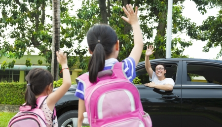 good bye: little girls say good bye with father in front of school