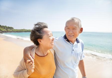 행복 한 아시아 노인은 해변에 산책