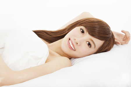 smiling young woman lying on the bed  photo
