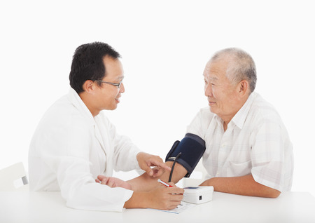 doctor measuring blood pressure of male patient photo