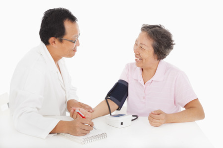 doctor examining woman: doctor measuring blood pressure of female patient