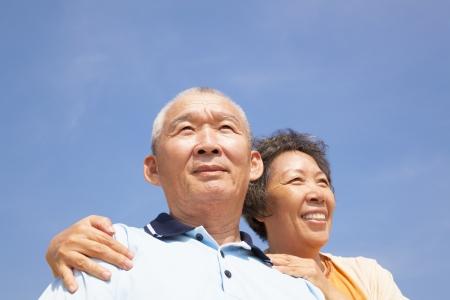 Happy elderly seniors couple with cloud background photo