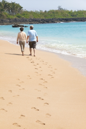 happy senior walking on the beach with footprint photo