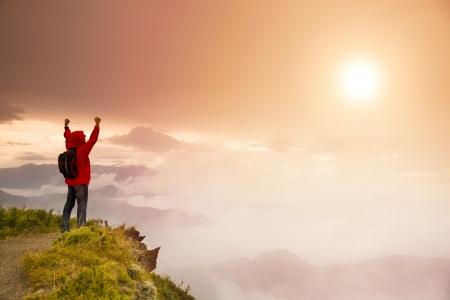 klimmer: Jonge man met rugzak staande op de top van de berg kijken naar de zonsopgang