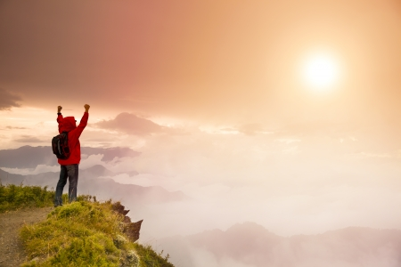 Young man with backpack standing on top of mountain watching\ the sunrise