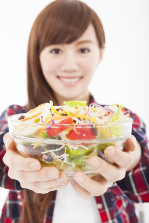 smiling young woman holding fruits and salad Stock Photo - 22676341