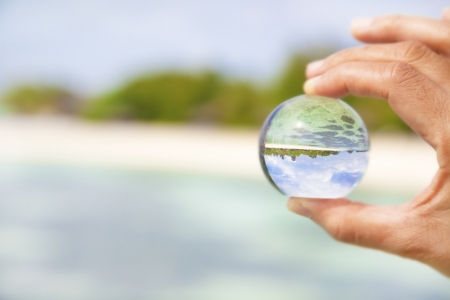 hand holding a little glass ball with beautiful beach view