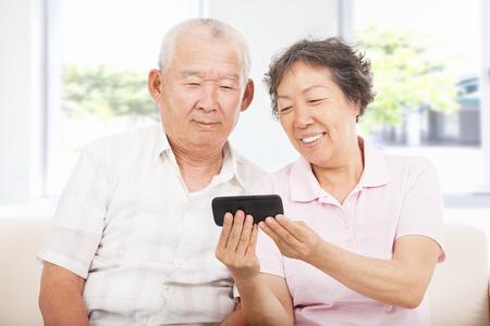 smart: gelukkig senioren kijken naar de smartphone