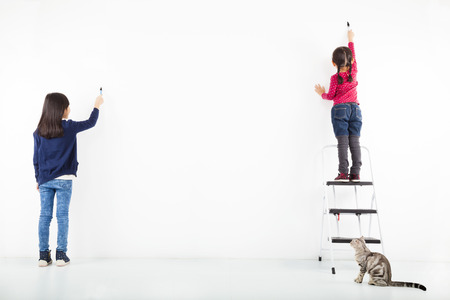 white walls: two kids drawing on the blank white wall