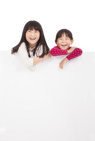 enfants qui rient: petites filles heureuses montrant tableau blanc sur un fond blanc Banque d'images