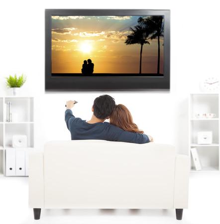 pareja viendo tv: pareja joven en el sof� viendo la televisi�n con control remoto