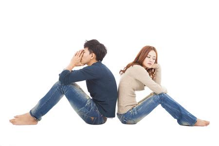 giovane coppia seduta back to back durante i conflitti photo