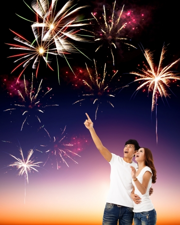 happy young couple watching the fireworks in the sky photo