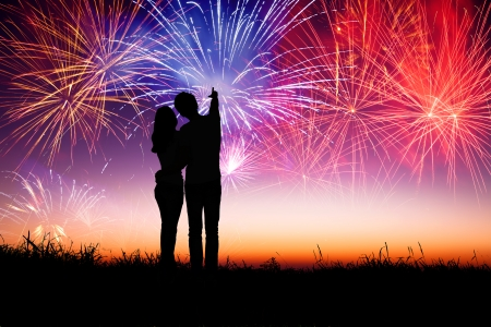 fireworks: young couple standing on the hill and watching the fireworks