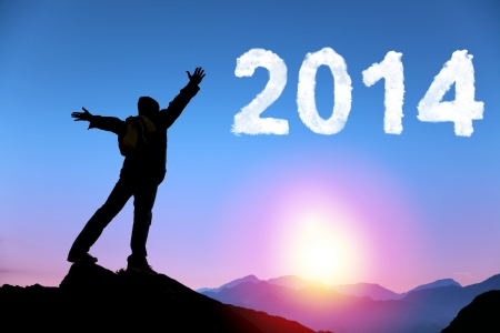 happy new year 2014.happy young man standing on the top of mountain photo