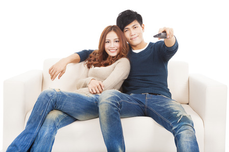 young couple on sofa watching TV with remote control photo