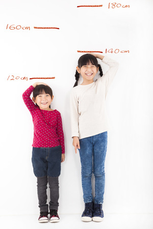 tall: Happy little girls growing up and against the wall