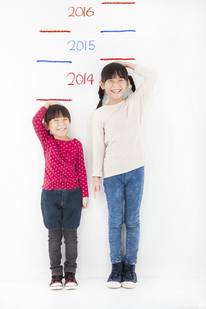 Happy children growing up  and against the wall photo
