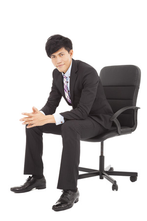 Young smart businessman  sitting in a chair photo