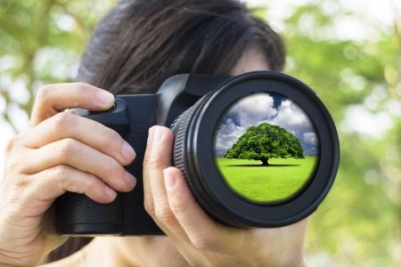 camera shutter: young Woman taking photo with green nature concept
