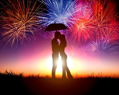 pareja abrazada: Pareja bes�ndose bajo el paraguas con fuegos artificiales en el cielo