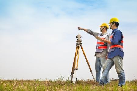 surveyor: Ingeniero topógrafo haciendo medida con la pareja en el campo
