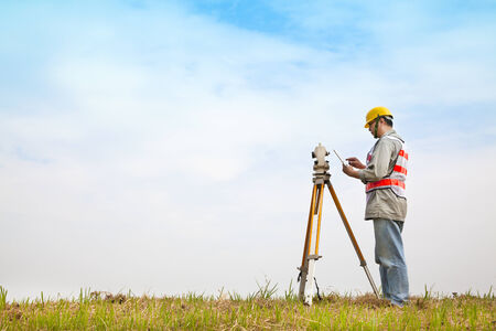 Surveyor engineer making measure on the field with tablet pc Stock Photo