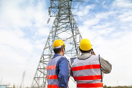 supervisores: dos trabajadores que usen casco protector trabaja en la estación de energía eléctrica Foto de archivo