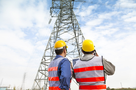 power: two workers wearing protective helmet works at electrical power station Stock Photo