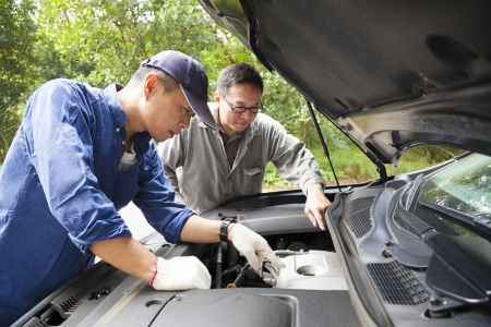 two Mechanics  fixing the car on the road photo