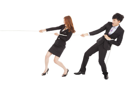 business man and woman playing tug of  war photo