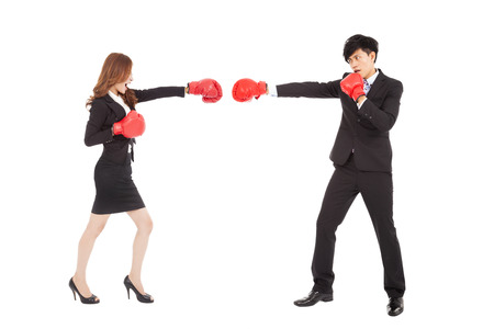 Business woman with boxing gloves having a fight with man photo